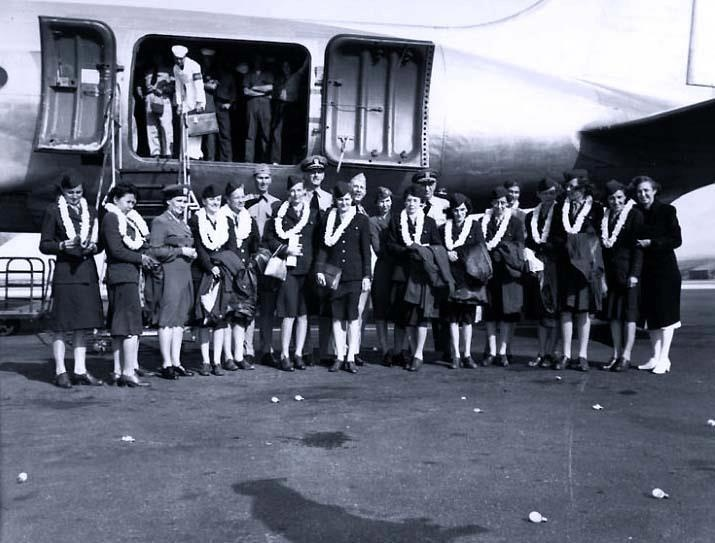 Navy Nurse Ex-Prisoners of War beside aircraft which brought them from the Southwest Pacific to Naval Air Station, Honolulu, then Territory of Hawaii, early March 1945. Pictured (left to right): Mary Chapman; Basilia Stewart; not identified; Edwina Todd; Susie Pitcher; Dorothy Still (Terrill); Mary Rose Harrington; Captain Camerer (to rear); Laura Mae Cobb; Dr Pollock (to rear); Margaret Nash; Eldene Paige; Goldie O Haver; Bertha Evans; and Helen Gorzelanski.