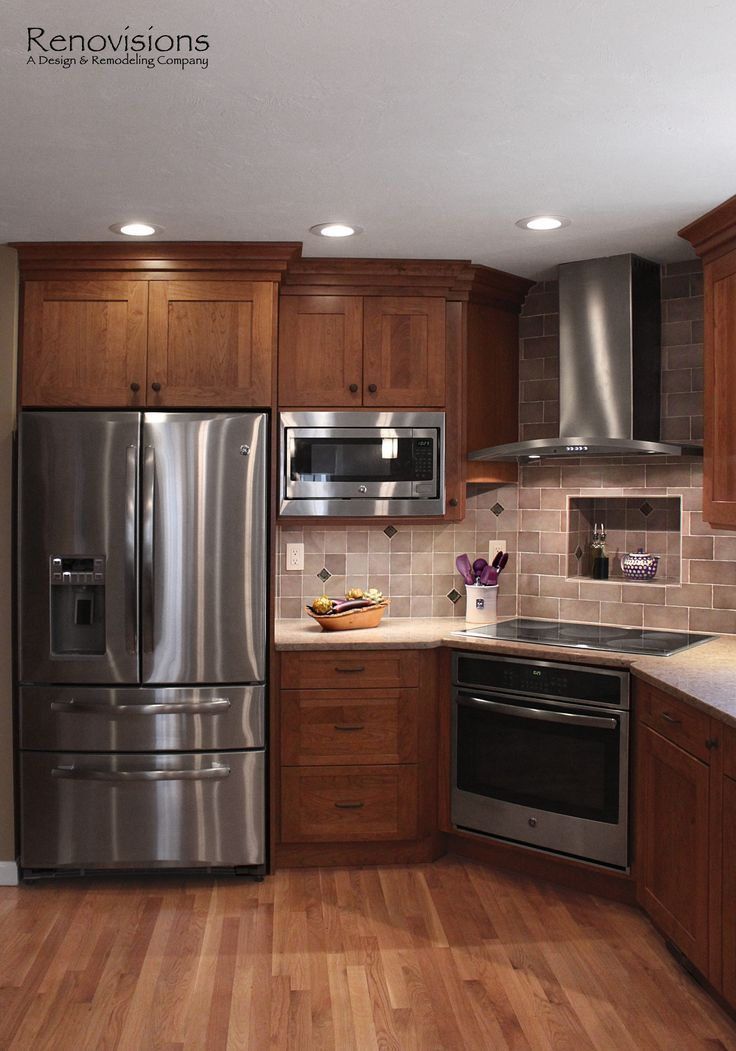 Kitchen remodel by Renovisions. Induction cooktop, stainless steel appliances, cherry cabinets, shaker cabinets, under cabinet lights, tuscan-clay-look porcelain tile backsplash, quartz countertop, hardwood floors, corner stove.