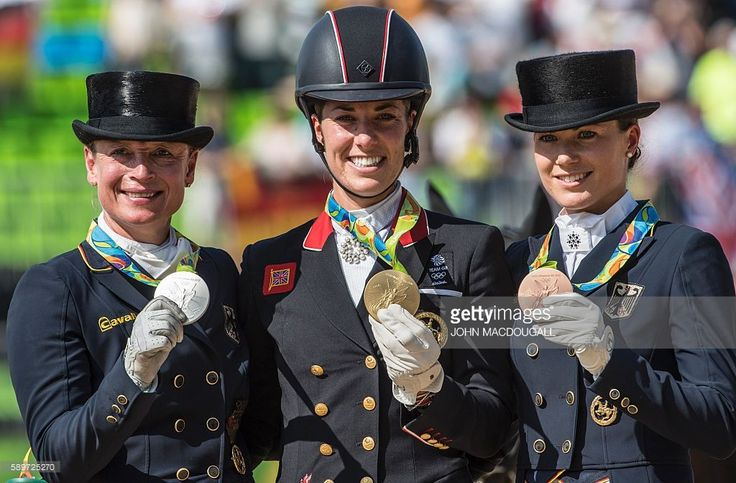Britain's Charlotte Dujardin (C), Germany's Isabell Werth (L) and Germany's Kristina Broring-Sprehe (R) show their gold, silver and bronze medals respectively during a victory ceremony after the Equestrian's Dressage Grand Prix Freestyle event of the 2016 Rio Olympic Games at the Olympic Equestrian Centre in Rio de Janeiro, Brazil on August 15, 2016. / AFP / John MACDOUGALL