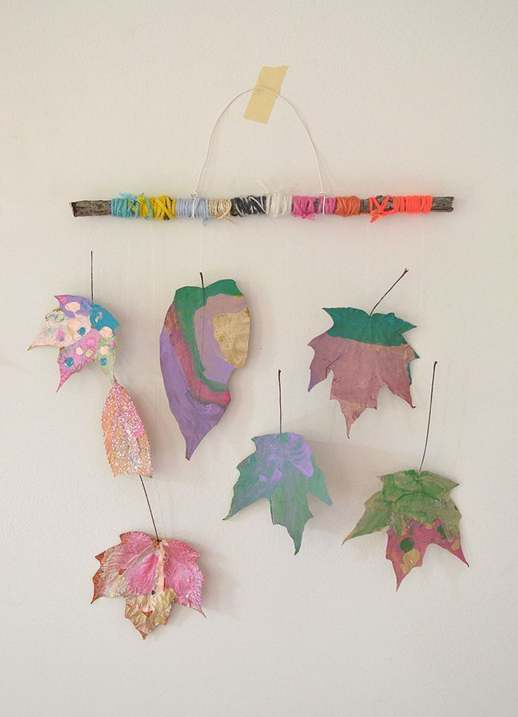 Children paint dried leaves and wrap twigs with yarn to make beautiful mobiles.