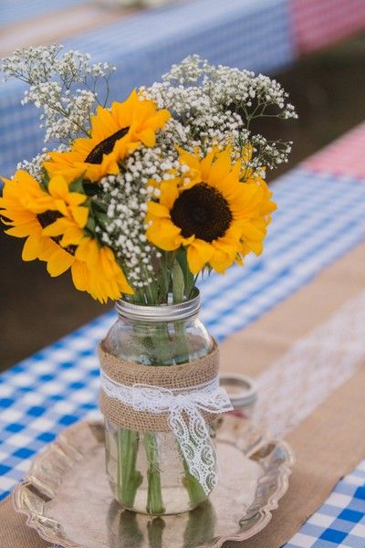 A picnic-themed reception table setting with checkered linens, burlap runners, and mason jar centerpieces with baby's breath and sunflowers! {@shelbyanneiam}