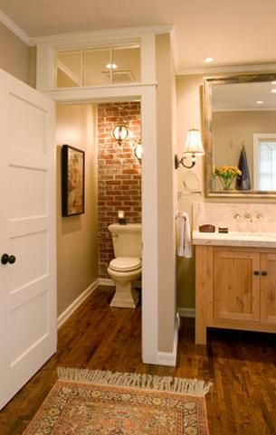 Small bathroom with wood floors, brick wall and glass panel at the top of the…