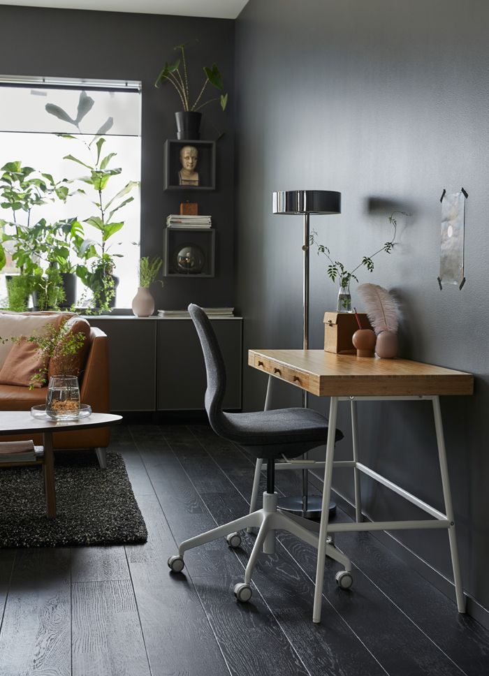Small desk with bamboo surface and white legs against a dark grey sitting room wall.