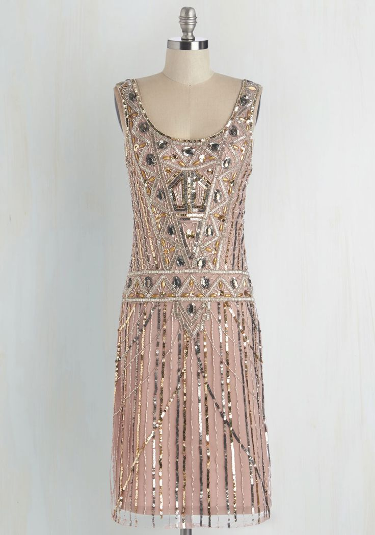Not even a ballroom filled with twinkling lights and fresh bouquets can compete with the elegance of this eye-catching dress! Glistening from scoop neck to hem - thanks to the geometric motif of metallic beads, sequins, and gems - this blush-pink frock complements the grandeur of the evening's fête.