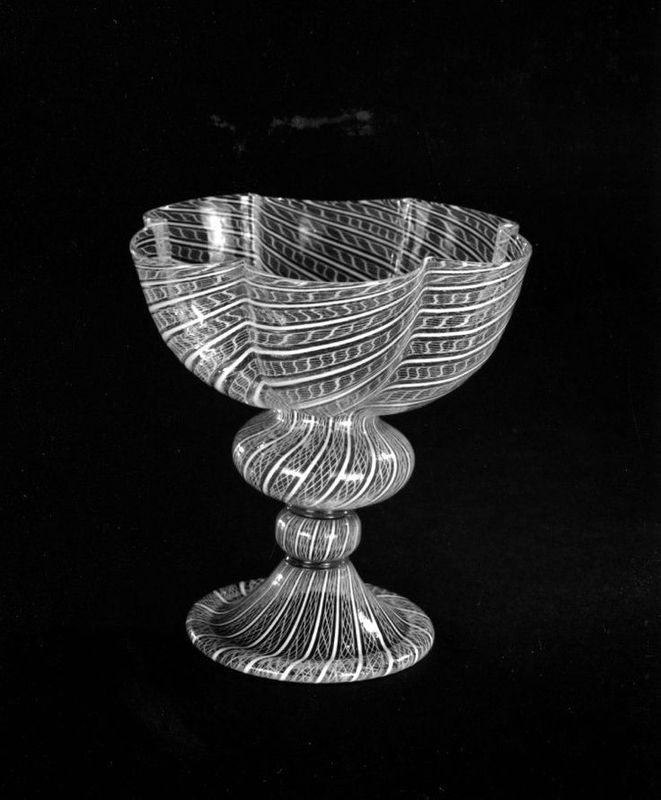 Goblet, glass, Venice, late 16th century; hemispherical bowl; six circular embayments; compressed bulb supported by knop and bell-foot; orna...