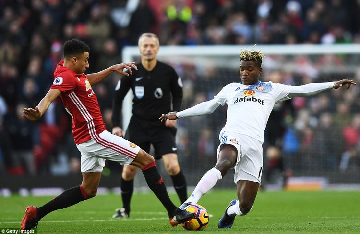 Jesse Lingard (left) and Didier Ndong stretch out a leg each to battle for the ball in the middle of the pitch