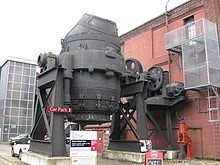 An original Bessemer steel blast furnace in Kenham, England. While seeking a way to make vast quantities of steel for artillery in 1855, Bessemeyer discovered that by blasting air into the vessel at high pressure during smelting impurities would burn off leaving high quality steel. It was the beginning of cheap, high quality steel, reducing cost by a factor of 10. In the US it created the steel industry, allowing steel rail to increase 5x at a fraction of the cost. It made the US a…
