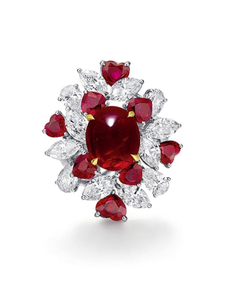 A 4.68 CARAT BURMESE RUBY AND DIAMOND RING. Set with an oval-shaped cabochon ruby weighing 4.68 carats, within a marquise-cut diamond surround, enhanced by heart shaped ruby details, mounted in 18K gold, ring size 6.