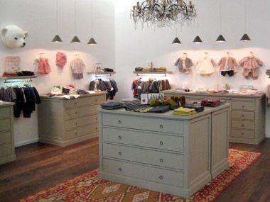 Bonpoint boutique, Chicago -- interesting color scheme for a kitchen: dark wood floors, green/gray cabinets, white walls -- with accents of red.