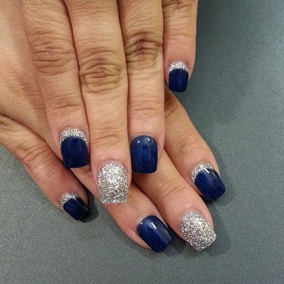 Exquisite looking blue themed nail art design. Midnight blue polish is used as the base color for this design coupled with silver glitter polish that strongly contrasts with the dark shade of the blue bringing life to the nails.: