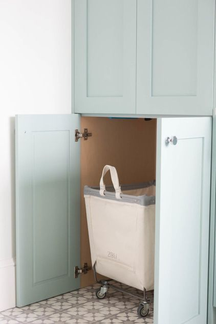 Clever cabinetry allows for the baskets to be rolled in beneath the laundry chute, which is also disguised by a cabinet. Whoever is doing laundry can roll the full bin over to the machines, replace it with an empty bin and use the other two for sorting.
