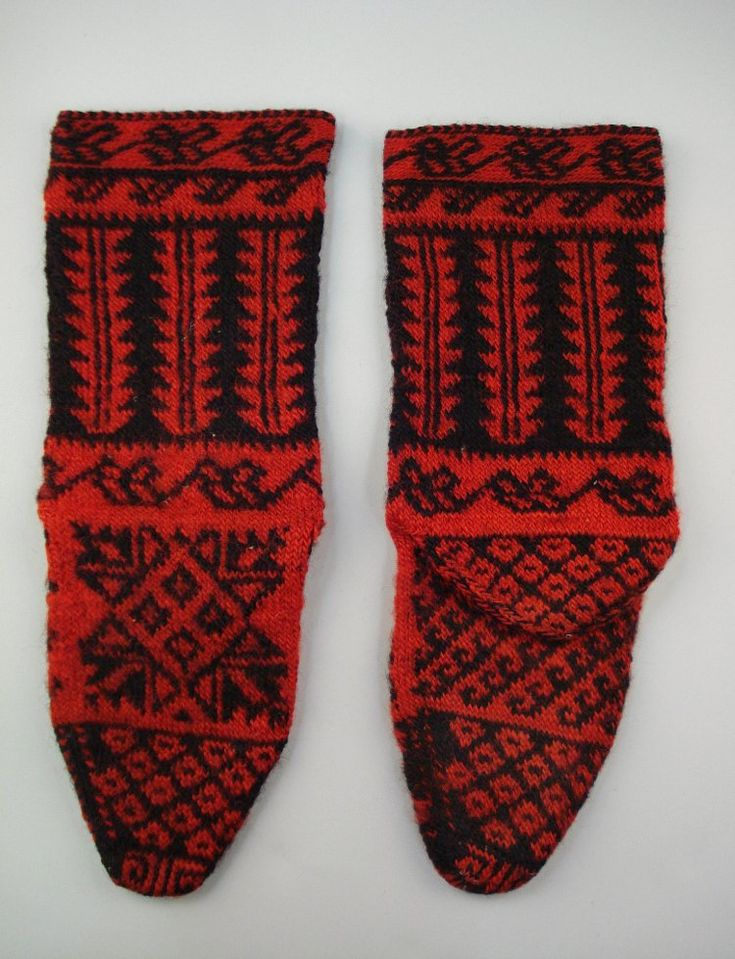 Pair of socks (carape), made from home produced wolloen thread, knitted in black and red, with horizontalanmd verticla geometric patterns in strabded knitting. Heel reinforced with cable stitch (?).