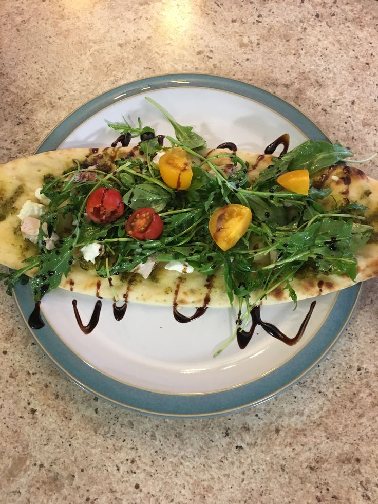 Pesto chicken and goat cheese flatbread with arugula and grape tomatoes