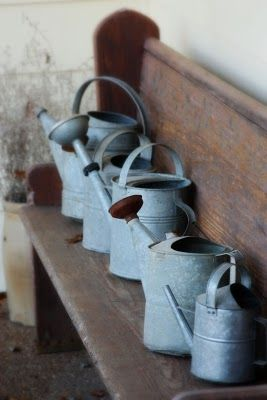 watering cans...neat idea for deck bench or front bench