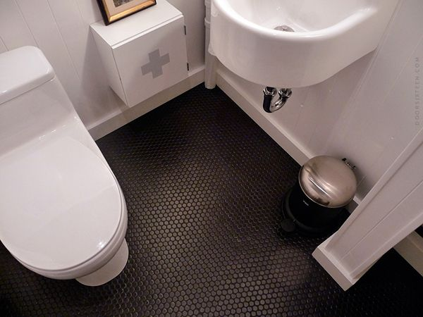 Matte black pennyrounds with charcoal grout on the bathroom floor, door sixteen discusses how well it works after 4 years. So we should do this!