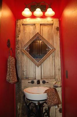 Love it, I should have done this! Old door used behind the bathroom sink..love the sink faucet mounted on the door The mirror is also attached. Red walls and ceiling really warm up this room!