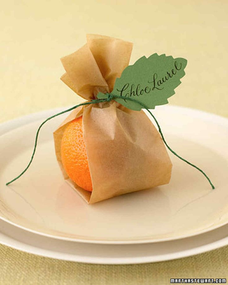 Clementine Place Cards | Martha Stewart Living - Mini oranges tucked inside strips of folded parchment paper bring warm color to your Mother's Day party table. Punch leaves from heavy paper, and have guests' names calligraphed. Tie on with waxed twine.