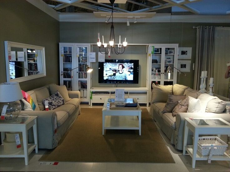 IKEA living room store display; beige sofa, white furniture, layered curtains - beige panels and white sheers; media wall