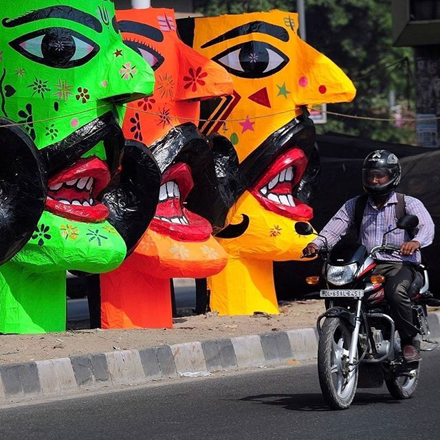 A motorcyclist passes effigies of Ravana, the demon king of Hindu mythology, on sale in preparation for the Dussehra Festival in New Delhi, October 20th 2015. Credit: AFP/Prakash Singh