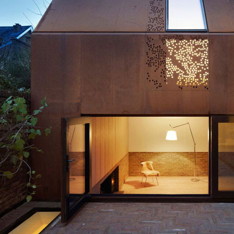 Piercy & Company has slotted a house behind an old stable facade in London, creating a pair of rusty gable walls with a glazed stairwell in between.