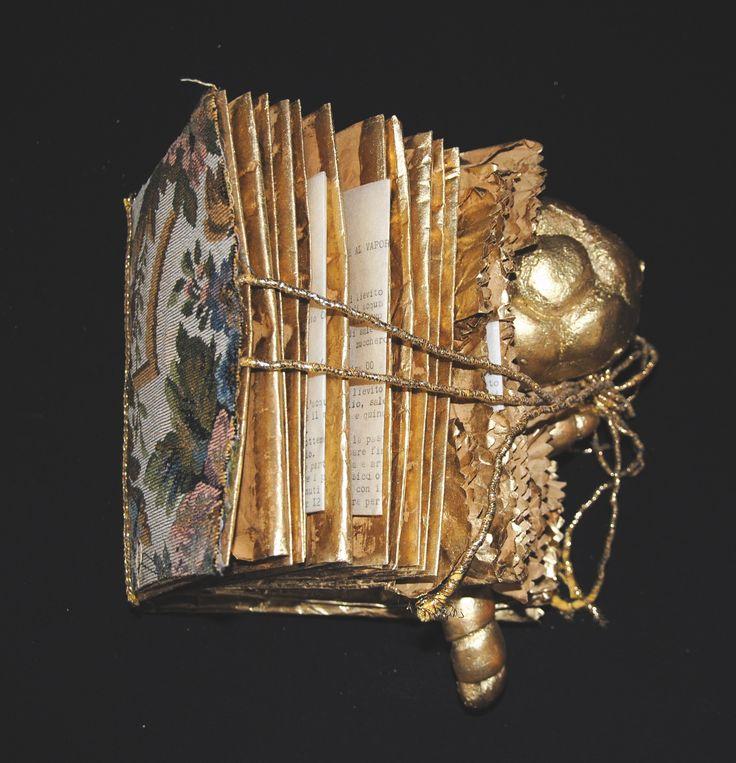 """Libro d'Artista """"Filigrano"""" Sacchetti per il pane riciclati si trasformano in libro, tra le sue pagine, impreziosite da broccati, rifiniture e polveri d'oro, sono custodite antiche ricette provenienti da tutto il mondo. Il pane, alimento che pur nelle sue numerose varianti è simbolo che accomuna tutti i popoli e tutti i fedeli di ogni religione.  Con l'arte si può educare il pianeta a non sprecare, a riutilizzare e servirsi consapevolmente dei mezzi che la natura ci offre."""