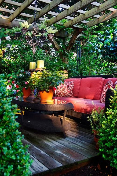 Outdoor Space under a pergola. Sitting area, surrounded by greenery, on a wooden deck.