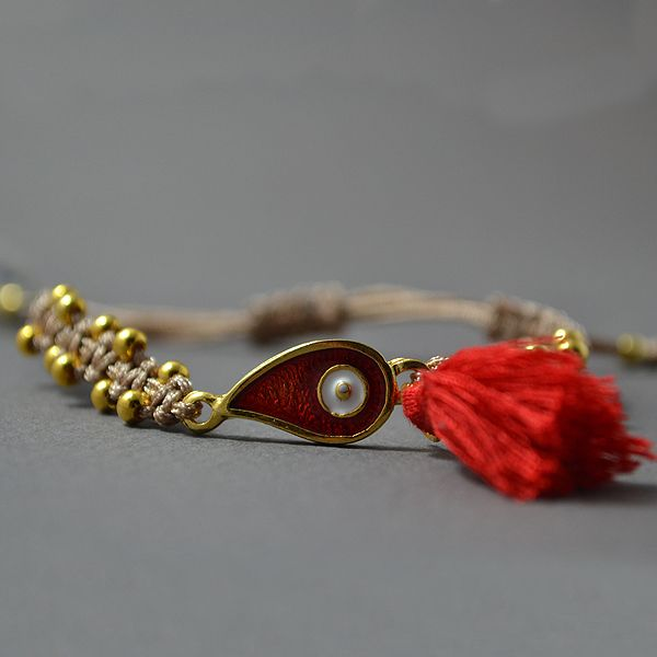"""Handmade Macrame bracelet """"Red eye"""".  Its made out of a beige waxed thread, small beads and a red tassel.  The bracelet is adjustable so it can fit to a wide variety of sizes."""