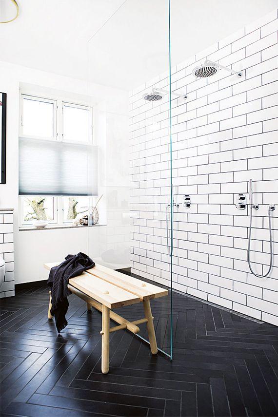 Black and white bathrooms | Double shower and herringbone tile floor. Photo by Tia Borgsmidt via Homelife.