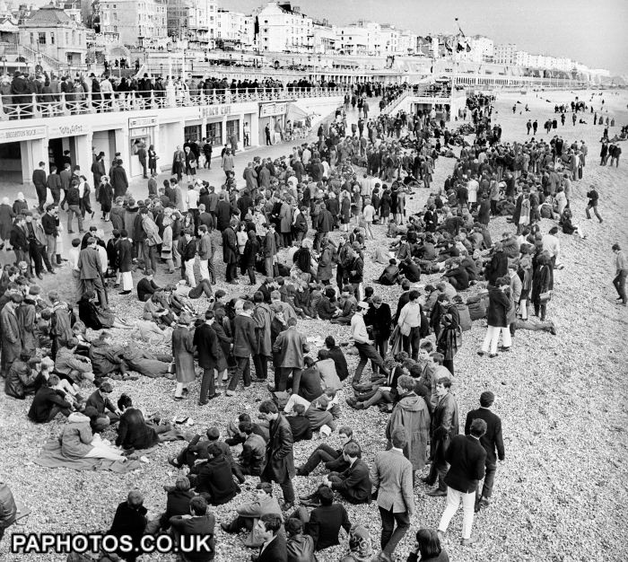 Mods and Rockers - Brighton - 1964. The Mods and Rockers bank holiday riots in Brighton. A large crowd of mods gathered near the Palace Pier on the beach in Brighton, a scene repeated a number of times at the Sussex resort, where gangs of mods and rockers clashed during Bank Holiday periods.