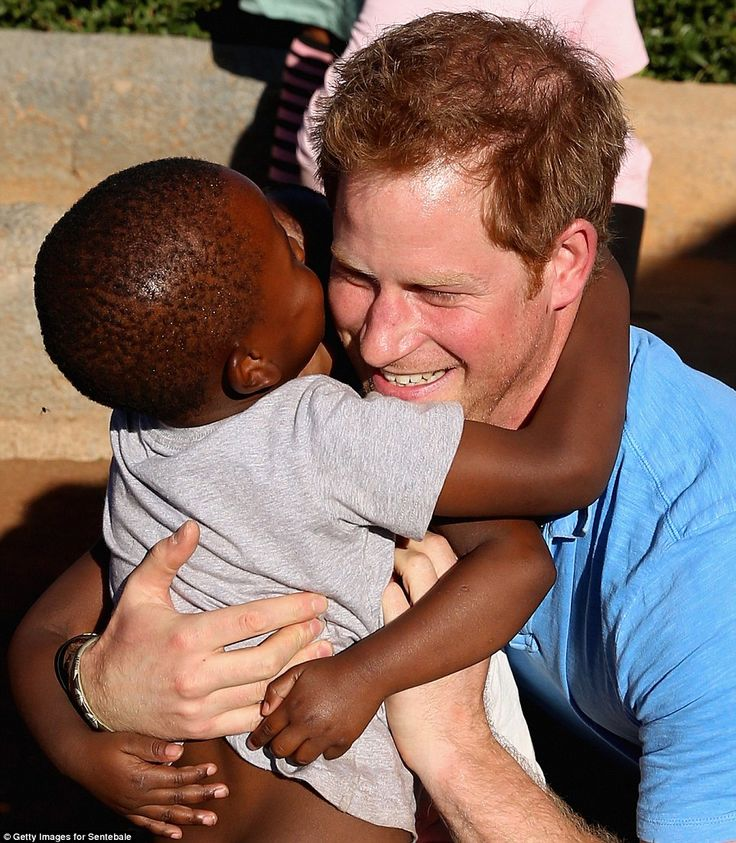 Big hug: One of the orphans living at the Phelisanong Children's Home in Pitseng, Lesotho, gives Prince Harry a big hug 2nd week of December 2014