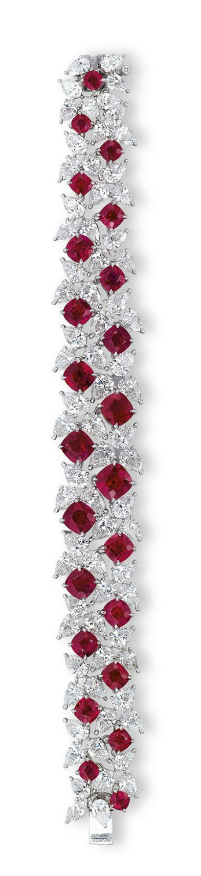A RARE RUBY AND DIAMOND BRACELET, BY FAIDEE The highly articulated pear-shaped diamond bracelet interspersed with twenty-three cushion-shaped rubies weighing approximately 23.21 carats total, the reverse accented by brilliant-cut diamonds, mounted in platinum, 17.0 cm long, in black Faidee case Signed and with maker's mark for Faidee