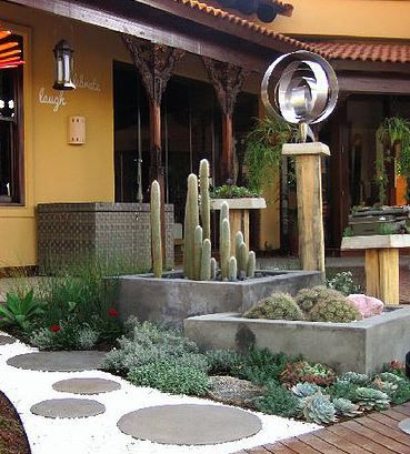 Custom made, concrete circular pavers, with rusted steel edging to contain gravel. Stainless steel wind mobiles on raw wooden pilar