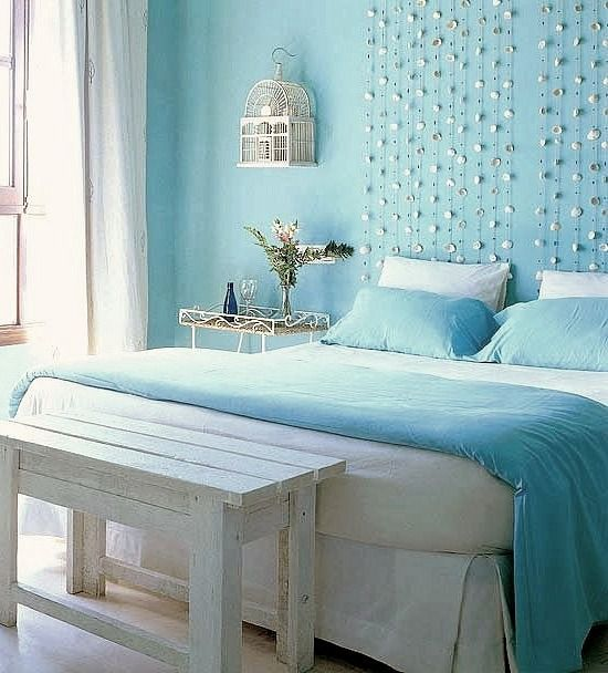 blue bedroom with seashell garland over bed http beachblissliving