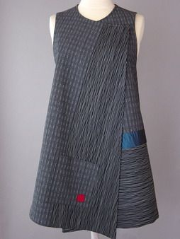 Long Round Neck Vest with Abstract Shapes and Teal Accent - Long Gray Vest with Intensely Stitched Lines Beautiful yarn dyed Japanese cotton is quilted to silk. A voile overlay is intensely stitched. Teal silk accent and pocket. This is a very wearable vest and desirable wardrobe piece. Easy to wear, has inside tie. Leave other side open or pinned. Size L