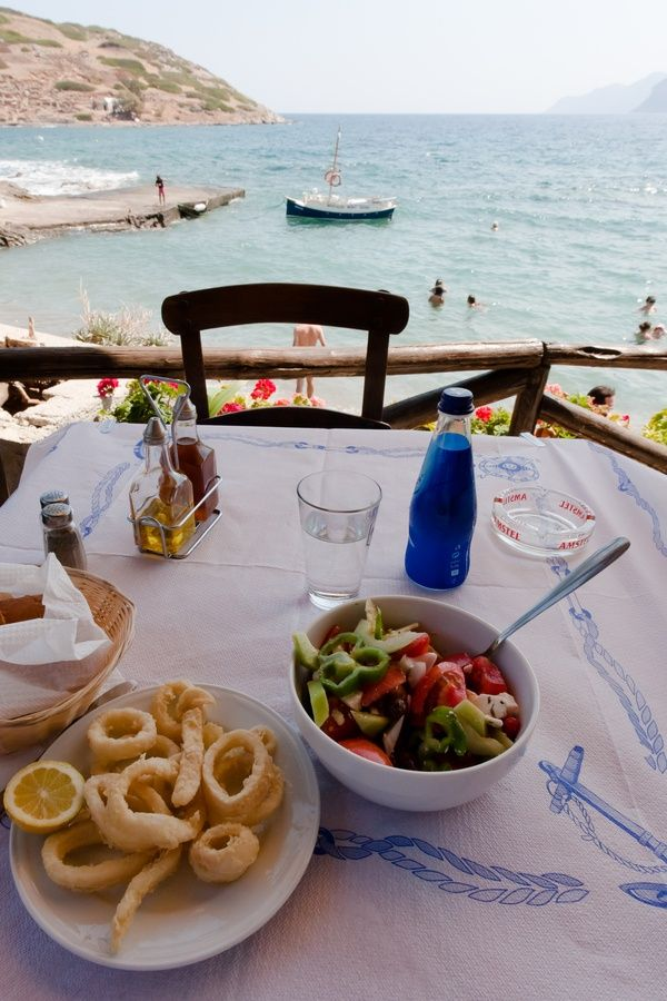 Crete - Typical Greek lunch by the sea. This is my perfect moment on any Greek journey: a plate of fresh Calimari and just-picked lemons, with a Greek Salad and a glass of local island wine. The table is close enough to the Aegean waters to hear them lapping at the harbour wall. And the sights and sounds of a busy little fishing harbour are spread out before me... Bliss!