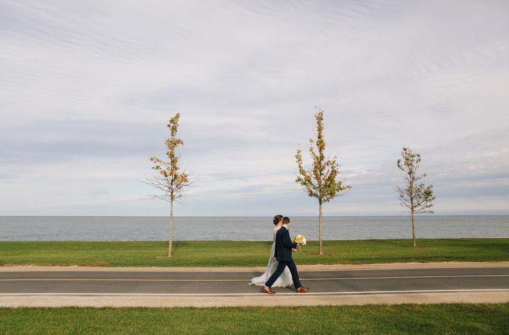 Brides walking on Lake Michigan Shore. Dapper bride, same sex wedding. Color inspiration. Traveling wedding photographer