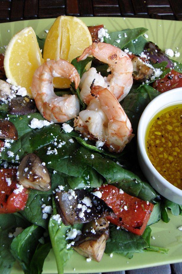 Ensalada de espinaca con camarones a la parrilla y un aderezo de mostaza Dijon con miel y cítricos.
