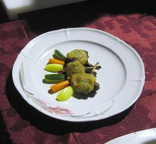 Lombo d' agnello in crosta croccante di funghi, con riduzione di sforzato e verdurine baby