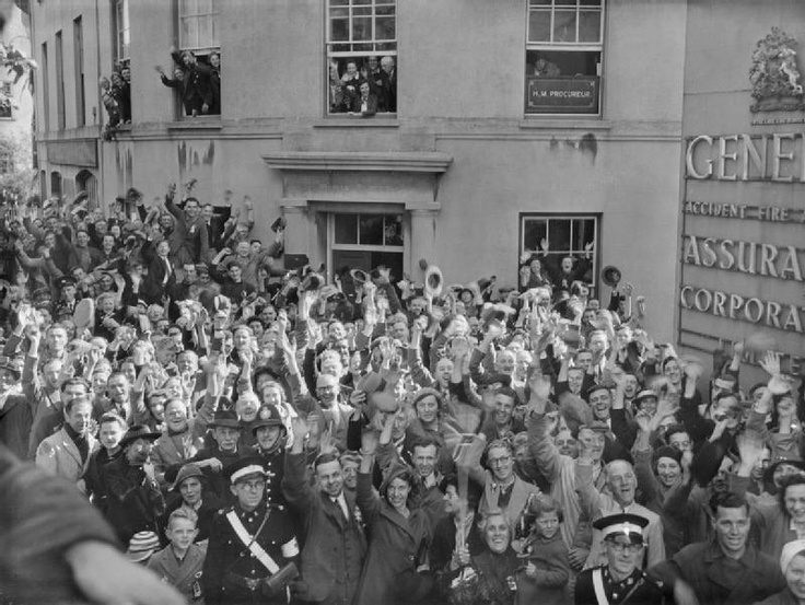 the Channel Islands were liberated by British forces after five years of German occupation. This photo shows crowds of people gathered ouside the General Assurance Corporation building in St Peter Port, Guernsey, to welcome the British Task Force