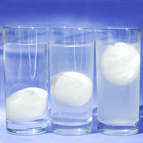 Drei Gläser mit Salzwasser und unterschiedlicher Dichte