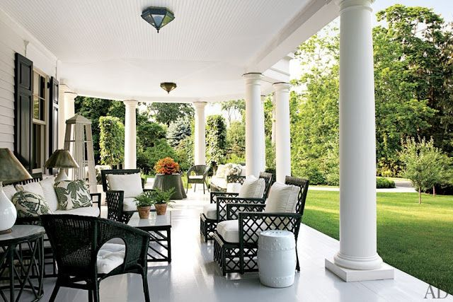 Black and white patio with black wicker furniture with white cushions, antique rattan chairs also with white cushions overlooking a lawn with small trees