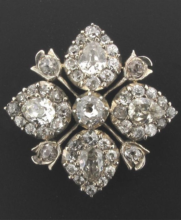 A George III diamond floral brooch. Each of the four petals centred with a pear shaped diamond within a surround of smaller cushion shaped diamonds in silver and gold (probably plated). Later gold brooch fitting. 2.5cm wide. With case by Wellby. #Georgian #antique #brooch