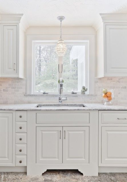 Beautiful kitchen with white kitchen cabinets, marble countertops