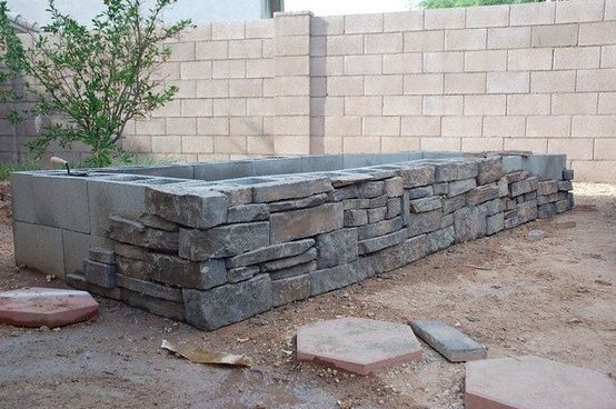 Stone veneer over concrete block bed. Could work for a retaining wall, too?