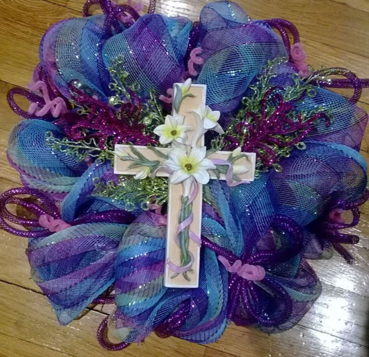 A Beautiful Deco Mesh Multi Colored With Glittery Green And Purple Leaves Placed On The Side Cross WreathEaster