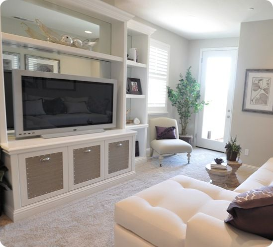 Built-in entertainment center with grasscloth inserts and nailhead trim.