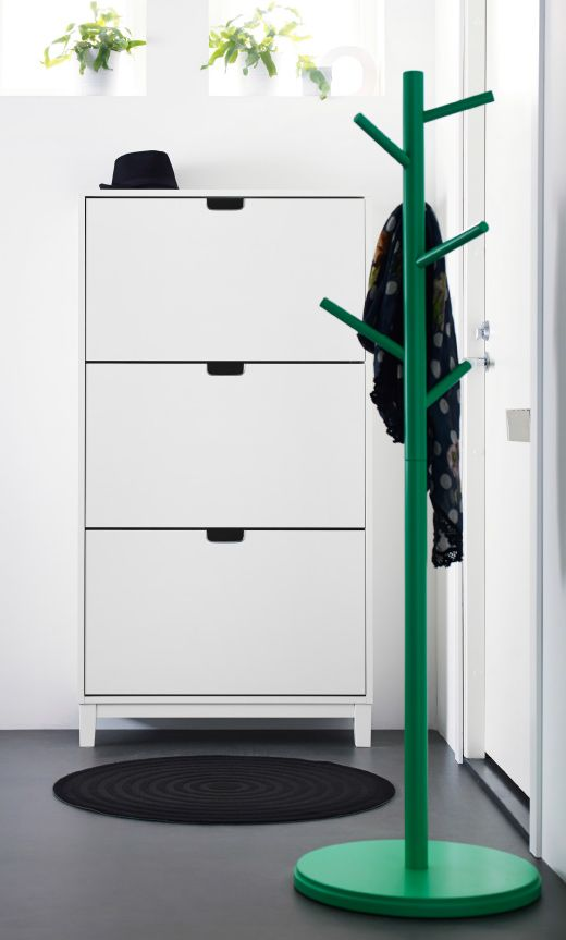 Green IKEA coat stand and tall, slender white shoe cabinet with three compartments.