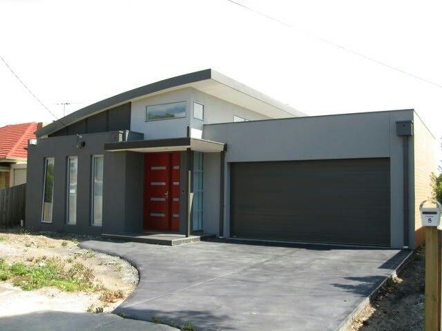 Grey rendered house with feature door - monument roof and garage door