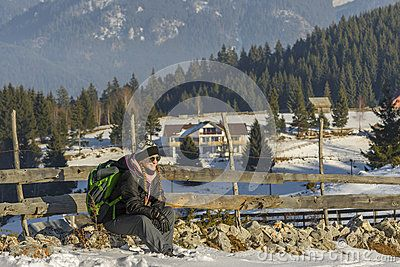 Lady tourist with backpack, sitting on a rock and admire the gorgeous mountain view near the Cheile Gradistei olympic complex on December 24, 2016 in Brasov county, Romania.