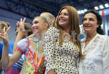 2246950 Russia, Kazan. 07/16/2013 Member of the Russian State Duma Committee on Physical Culture, Sport and Youth Affairs Alina Kabayeva, 2nd from right, and President of the Russian Gymnastics Federation Irina Viner-Usmanova, right, pose for photographs with the Russian athletes after the medal ceremony for rhythmic gymnastics at the 27th World University Summer Games in Kazan. Iliya Pitalev/RIA Novosti